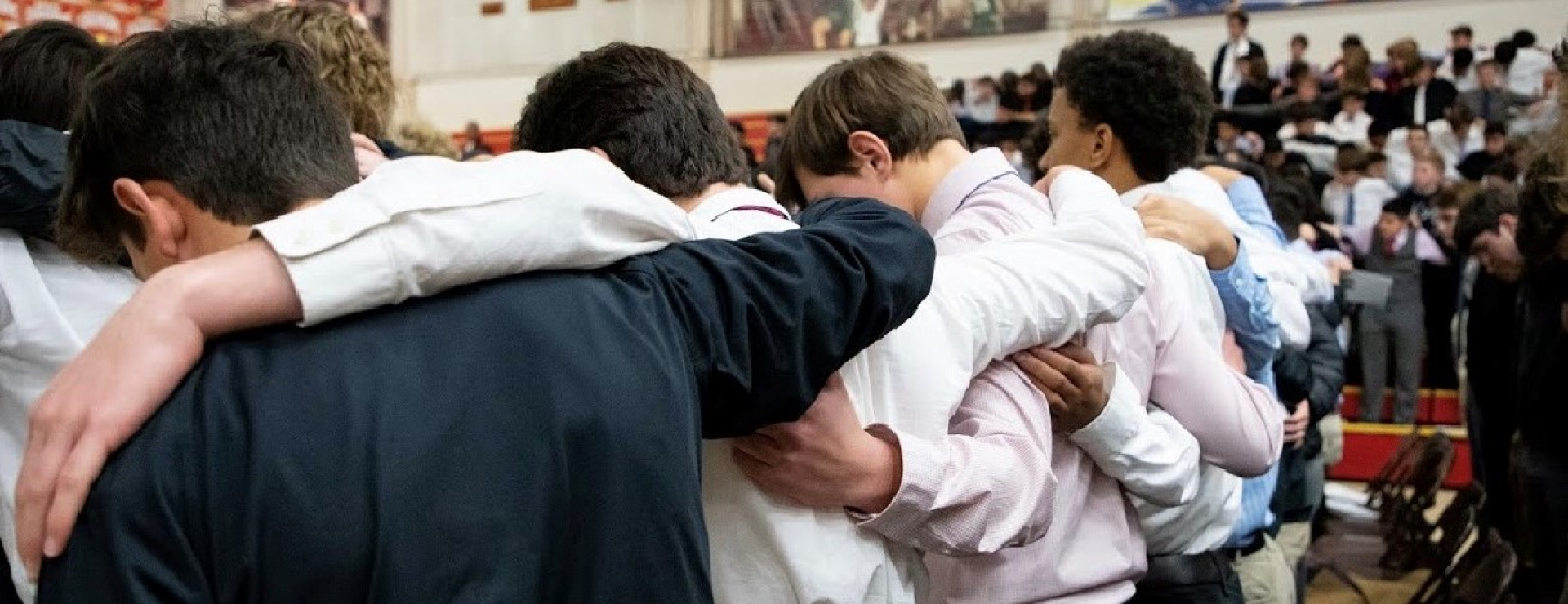 boys at Mass with hands over shoulders praying