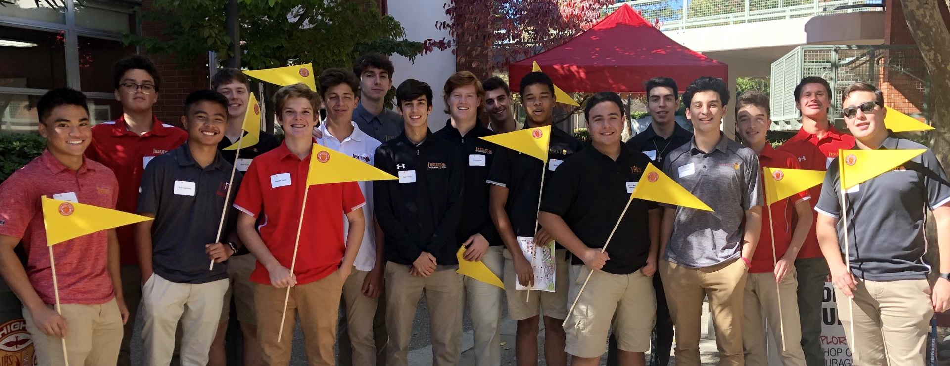 Group of student Open House tour guides with their bright yellow flags on poles.