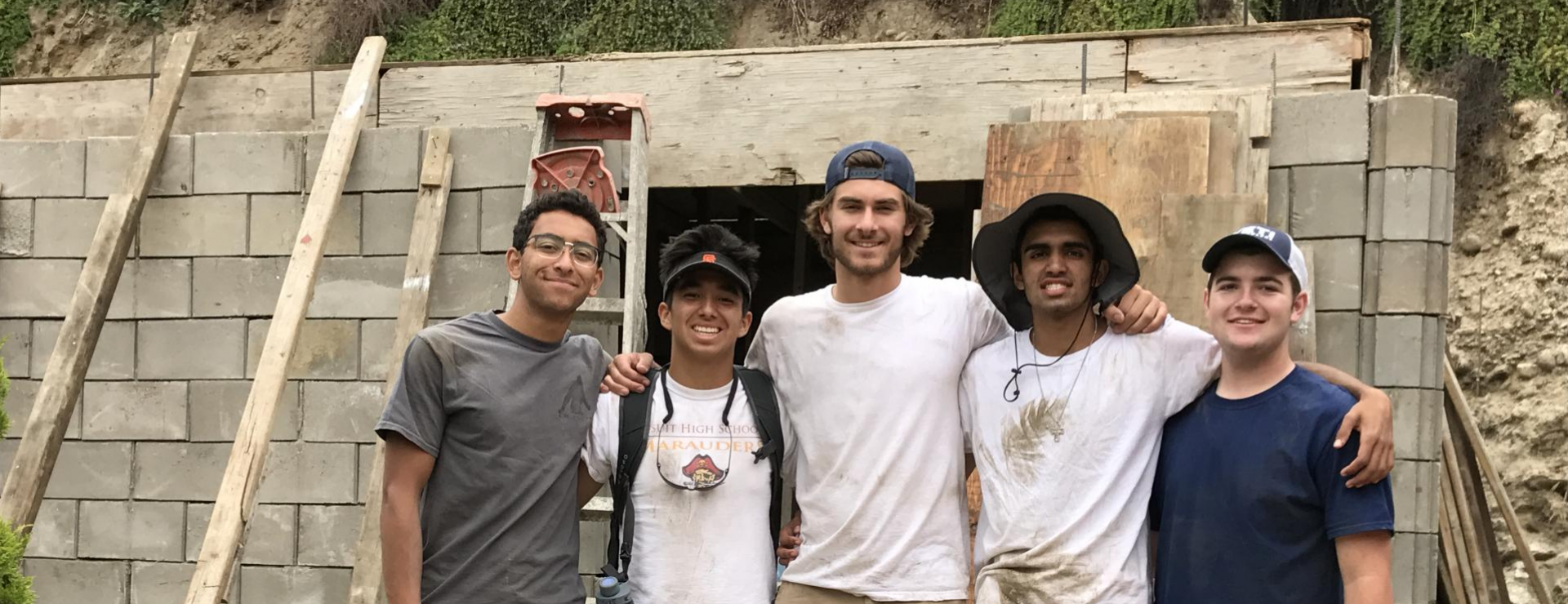 Group of 5 students smiling and standing in front of a wall being built in Tijuana Mexico