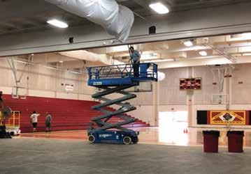 Scissor lift with man working on HVAC in the middle of the gym.