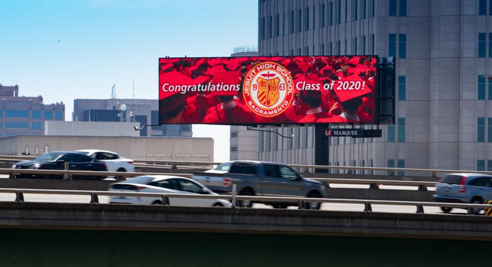 "Photo of a digital billboard showing an image of red graduation robes and caps and the jesuit seal with ""Congratulations"" message"