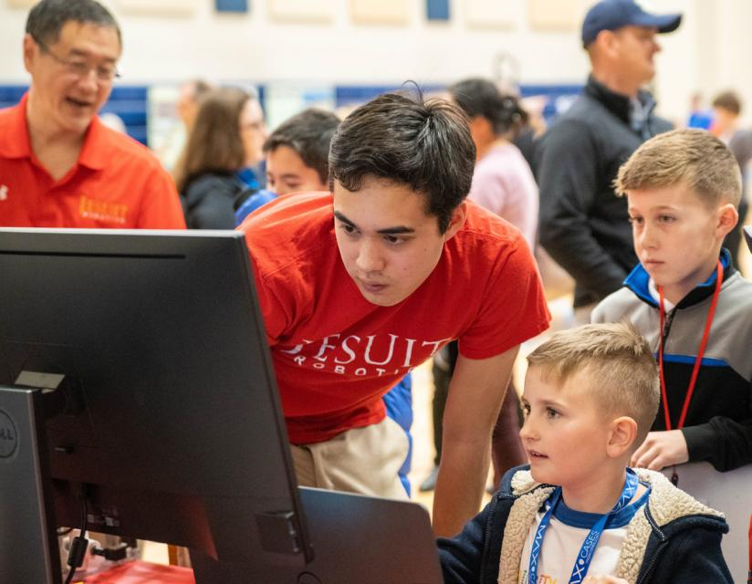 Robotics team member demonstrating movement on computer to young boy