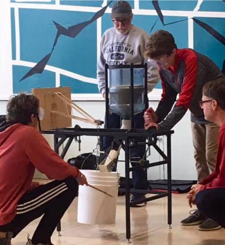 Image of students and instructor standing around a table working on large science project