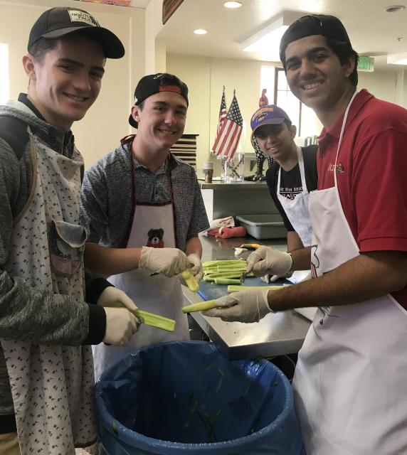 Four students prepping food in a kitchen