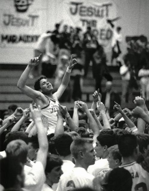 historic black and white photo in the gym with team holding up a player, arms upraised in victory