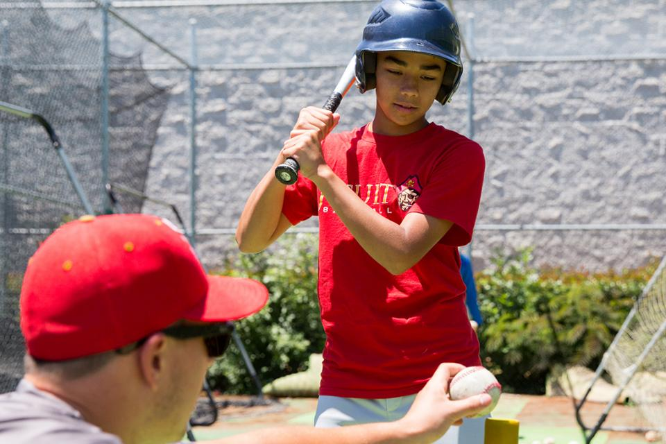 Image of young child at bat getting baseball instruction