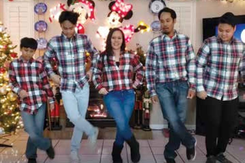 Family doing a line dance, wearing matching flannel.