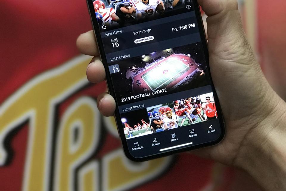 hand holding a mobile phone with athletics app open