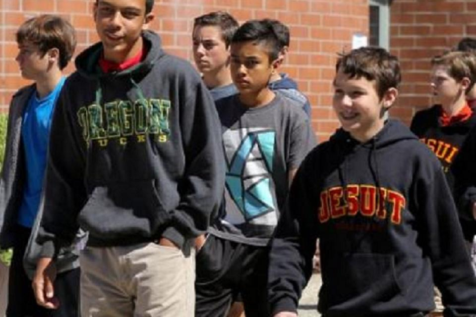 Group of young boys walking on campus and smiling.