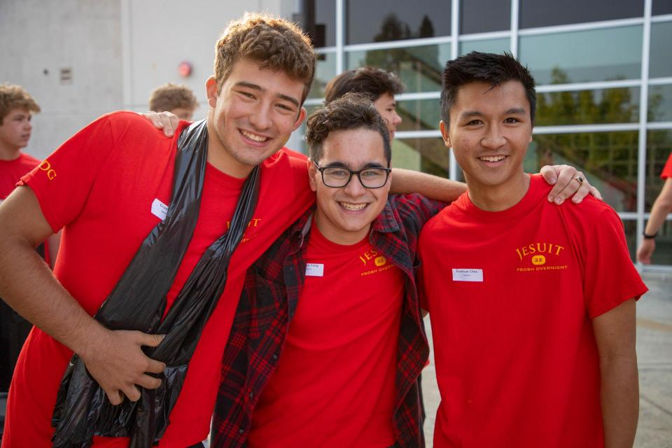 Three students smiling in Frosh Overnight shirts