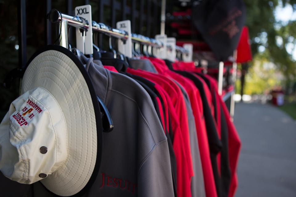 Image of shirts with logo and hat on rack in front of Marauders Cove