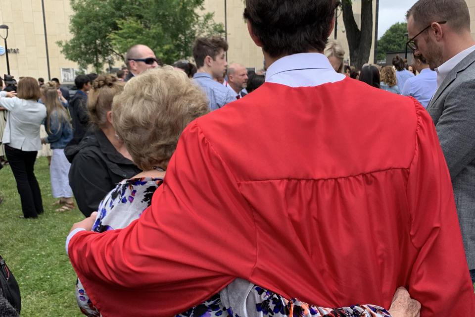 Shot from behind, a grandmother with arm around a graduate in robe