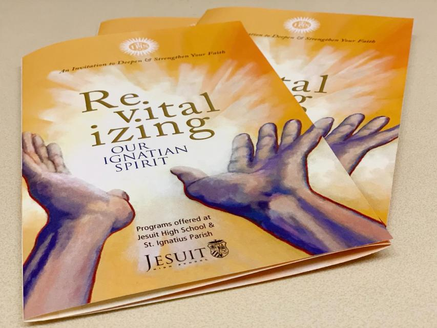 "Brochure cover featuring open hands with a burst of light and words ""Revitalizing our Ignatian Spirit"""