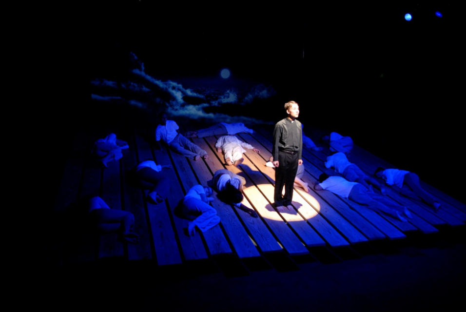 Dark stage with actors laying down on plank floors, while one student stands in spotlight.