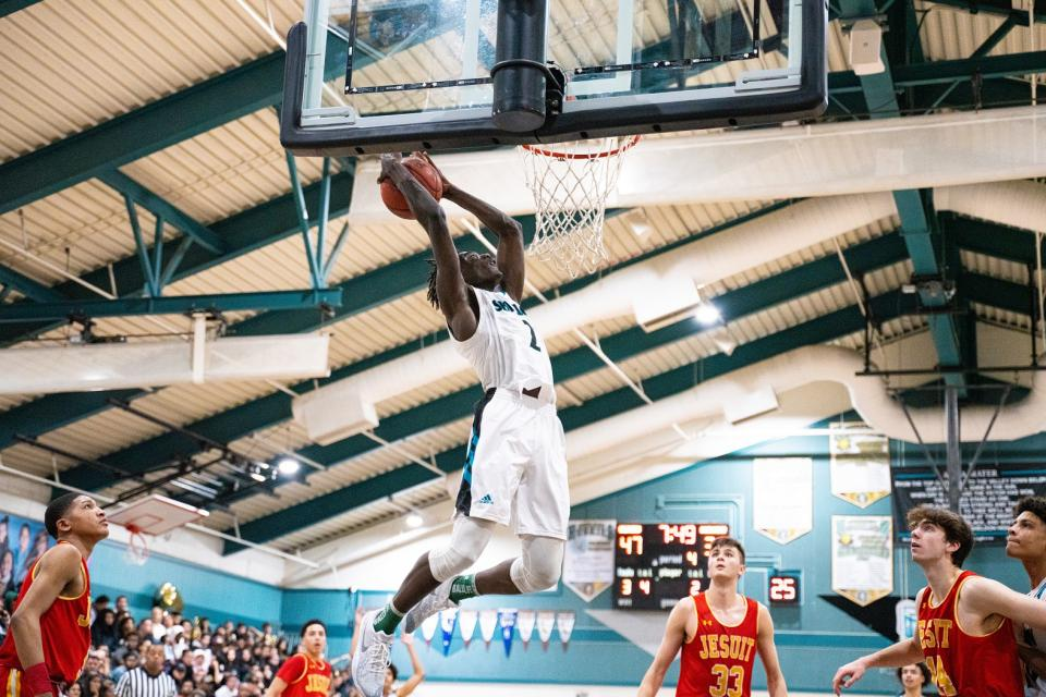 Sheldon senior guard Xavion Brown attempts a dunk in the fourth quarter of a basketball game between Jesuit and Sheldon on Saturday, Feb. 1.
