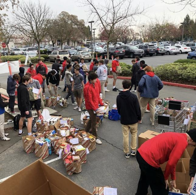 Full parking lot with students unloading cars and baskets full of canned goods