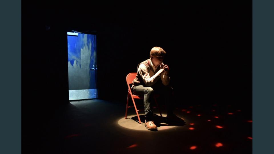 Student in spotlight sitting thoughtfully in folding chair on dark stage.