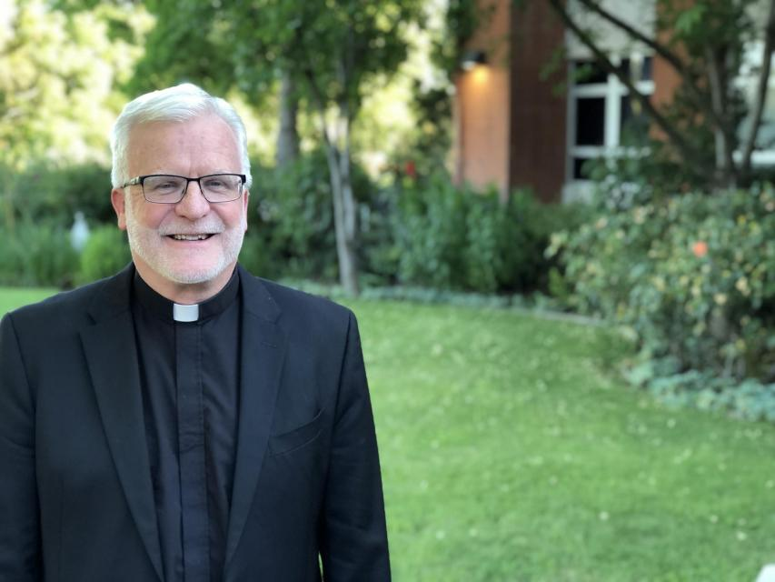 Image of Rev. John P. McGarry, S.J. on campus in front of garden