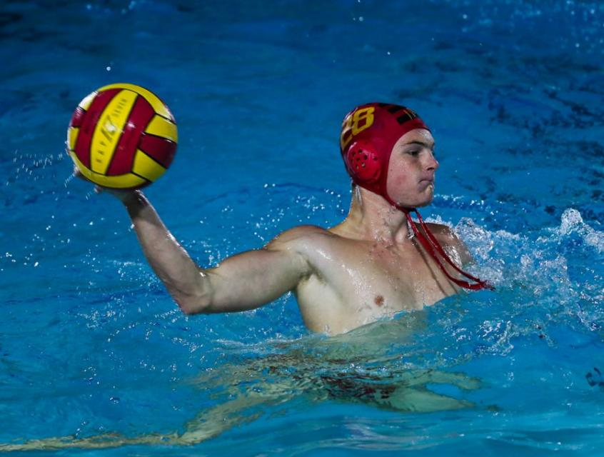 Water polo player in pool with ball in one hand.