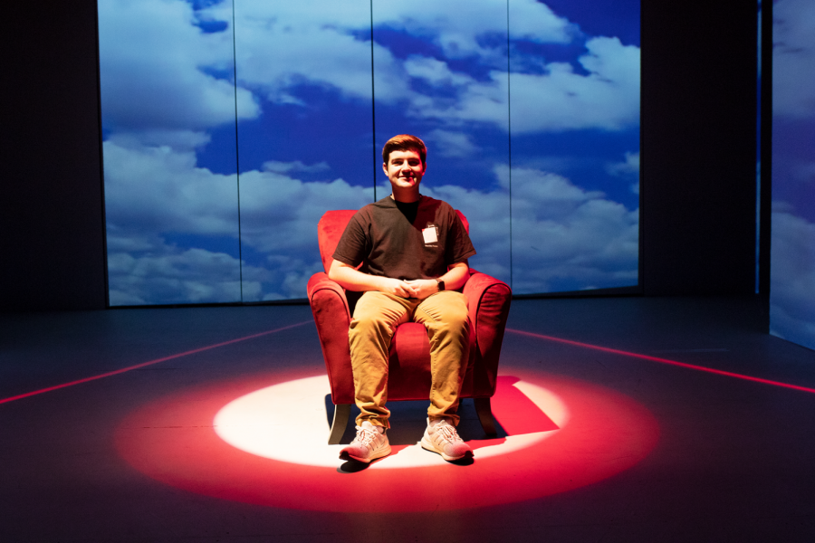 Student sitting alone on stage in red arm chair with dramatic lighting and staging.
