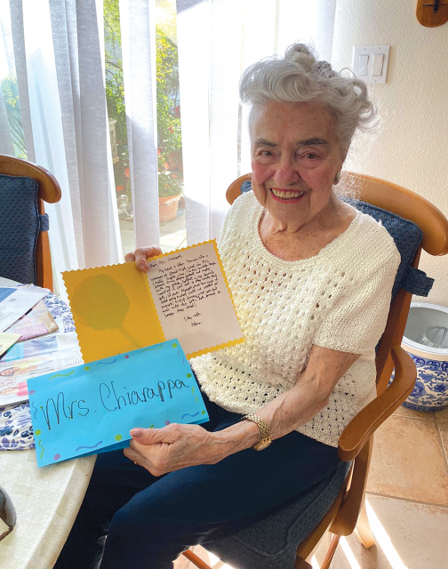 Elderly woman sitting and smiling while holding a card in each hand.