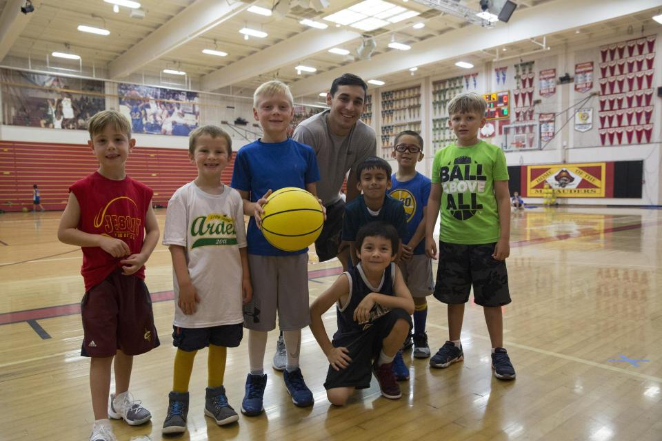Group of young kids smiling in the gym holding a basketball.